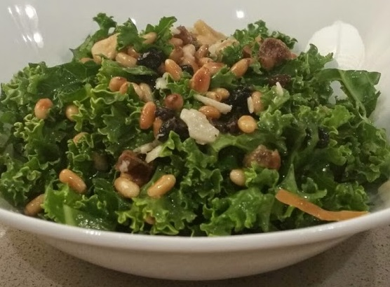 Kale Salad w/ Toasted Pine Nuts, Currant, Dates, Garlic and Parmesan in a Honey Citrus Vinaigrette | www.whiskeyandchanel.com